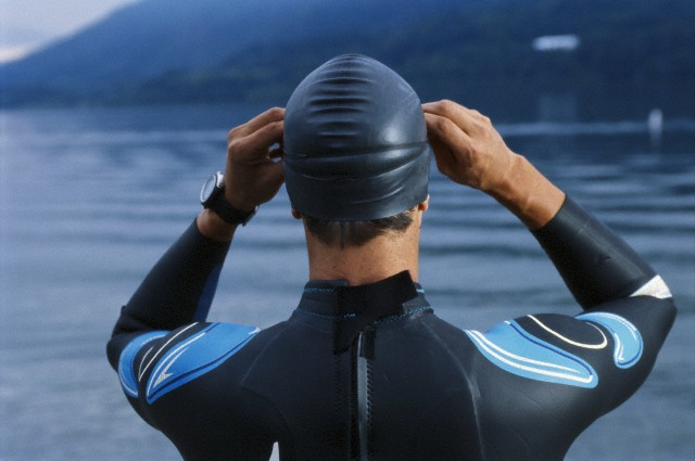 Young male triathlete adjusting swim goggles, close-up, rear view
